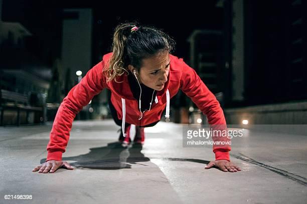 young athlete doing push-ups in park - atlete stockfoto's en -beelden