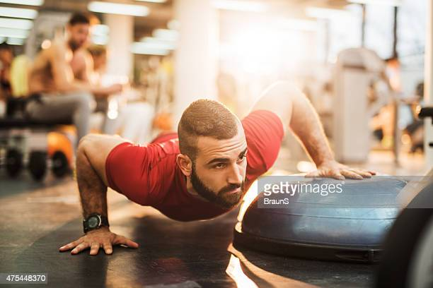 Young athlete doing push-ups with exercise equipment at gym.