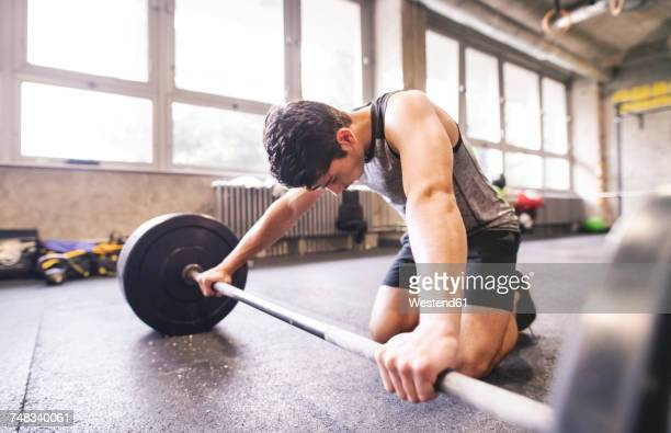 Young athlete exercising with barbell in gym