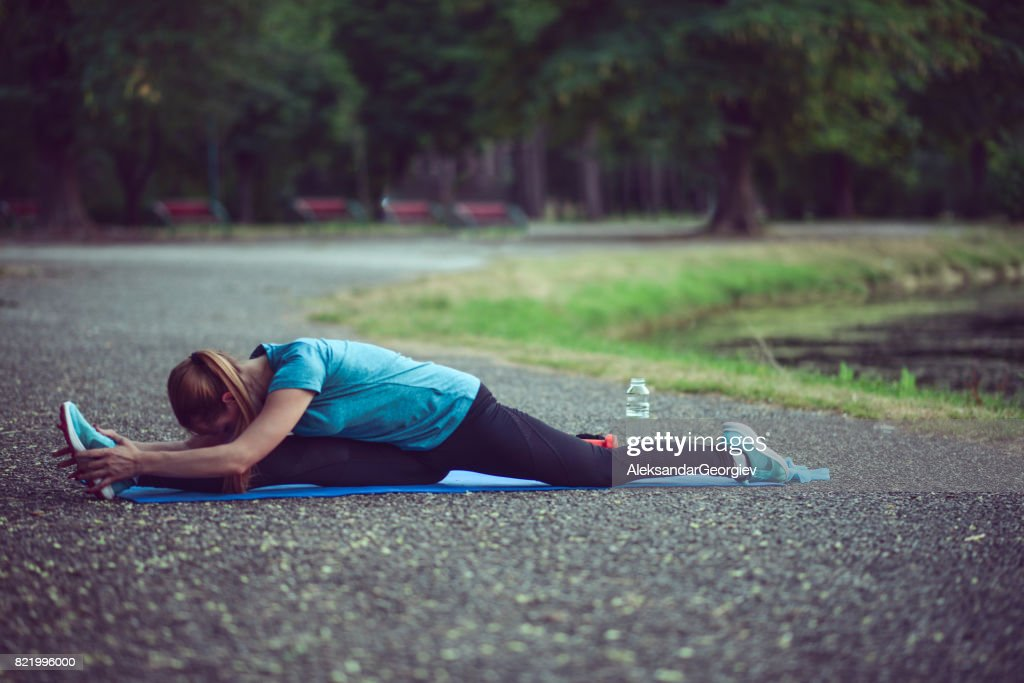 Young Athlete Female Doing Full Split Stretching on Exercise Mat in City Park : Stock Photo