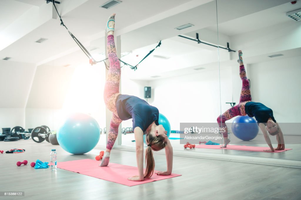 b509f18b4f2e0 Young Athlete Female Practising Yoga in One legged Wheel Pose : Stock Photo