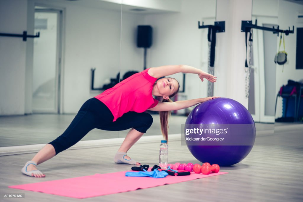 Young Athlete Female Practising Yoga Pilates In Front of Gym Mirror : Stock Photo