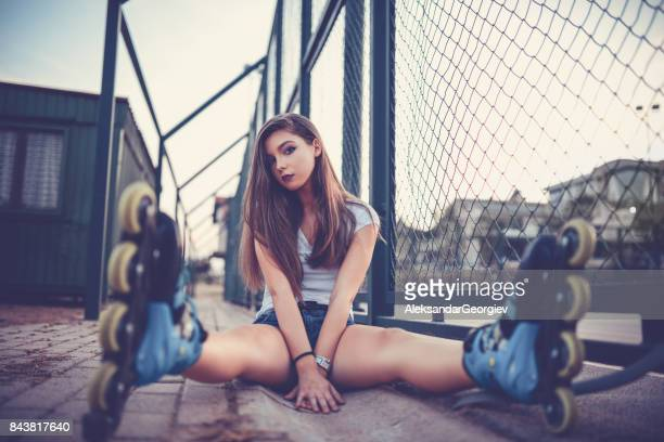 young athlete female rollerblader sitting and posing in skate park - legs apart stock pictures, royalty-free photos & images