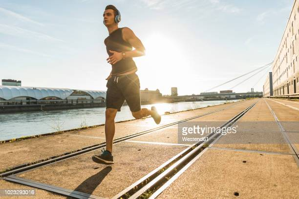 young athlete jogging in the city at the river - jogging stock pictures, royalty-free photos & images