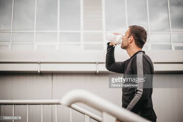 Young athlete man drinking water