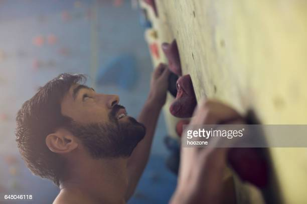 Young athlete man on rock climbing wall
