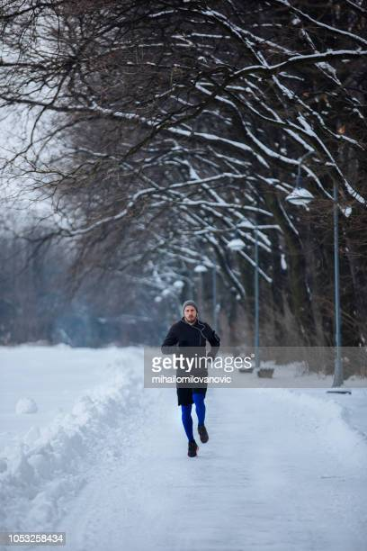 young athlete man running at winter
