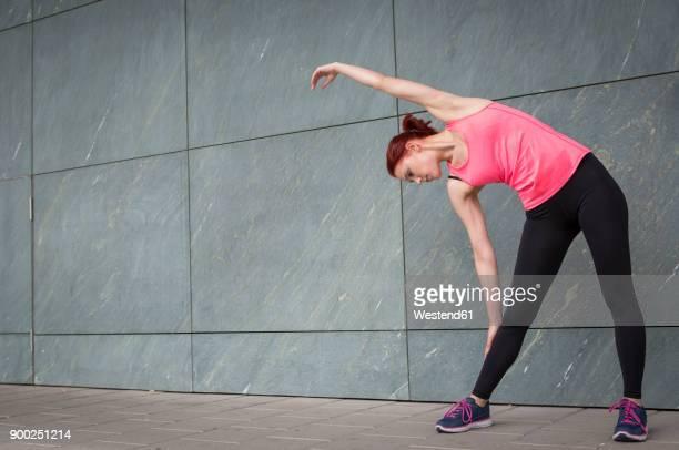 young athlete stretching outdoors - aufwärmen stock-fotos und bilder