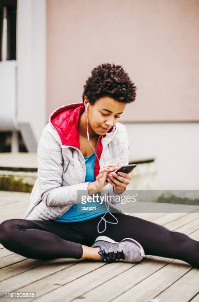 young athlete warming up for exercise, listening to music - center athlete stock pictures, royalty-free photos & images