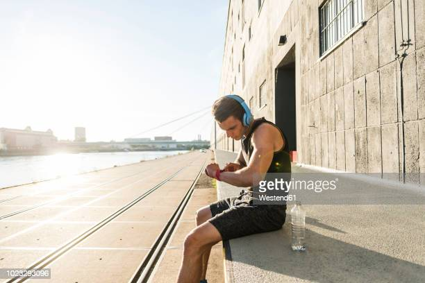 Young athlete wearing headphones, sitting on a wall, checking smartwatch