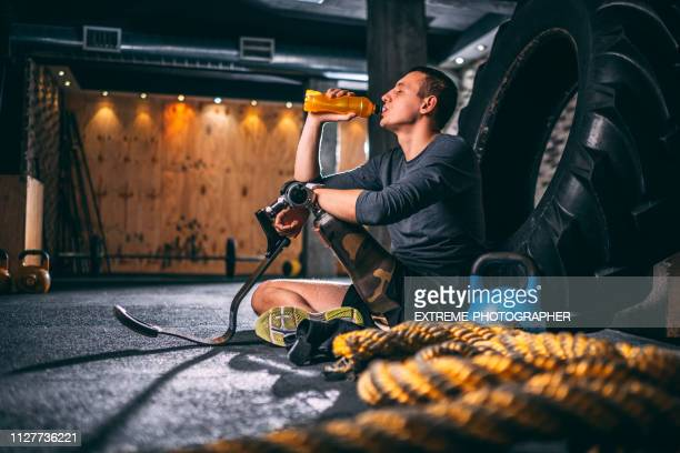 young athlete with a let prosthetic drinking an energy drink and relaxing after a gym exercise in a gym - energy drink stock pictures, royalty-free photos & images