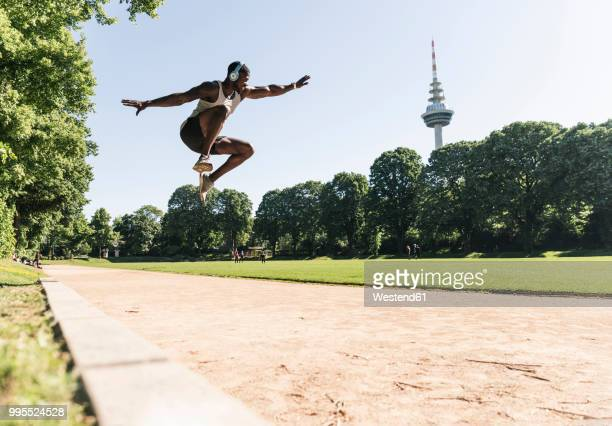 young athlete with headphones, listening music, training long jump - men's field event stock pictures, royalty-free photos & images
