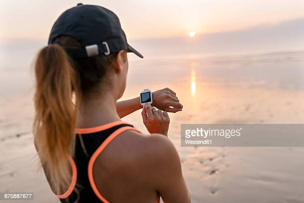 young athlete woman looking the smartwatch on the beach at sunset - checking sports stock pictures, royalty-free photos & images