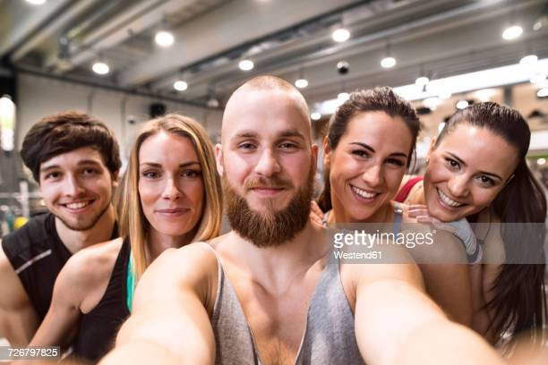 Young athletes having fun in the gym, taking selfies