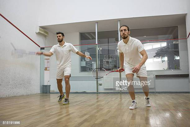 Young athletes in white playing squash on a court.