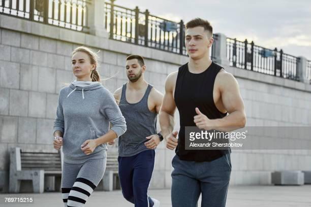 Young athletes jogging against bridge