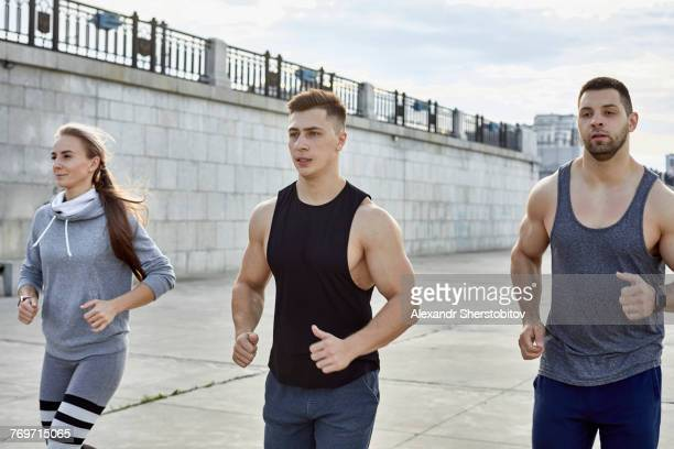 Young athletes jogging on footpath against wall