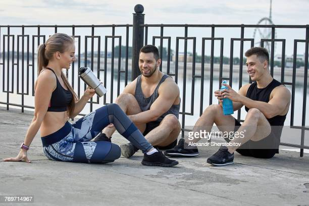 Young athletes resting on footpath by railing