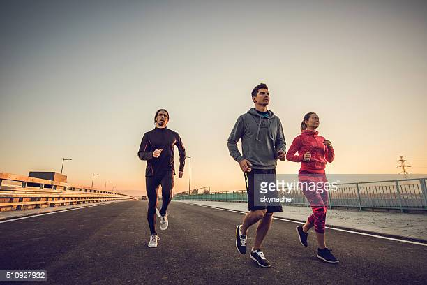 Young athletes running on a bridge at sunset.