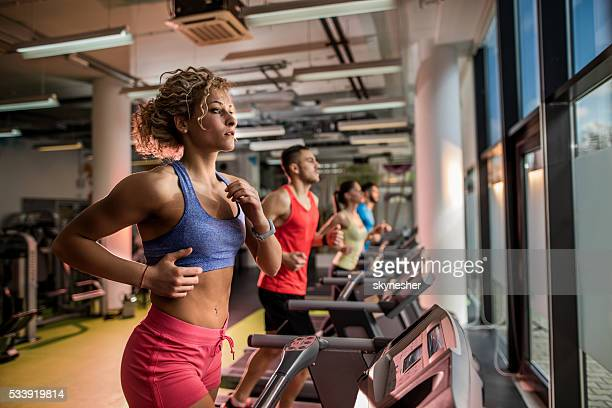 Young athletes running on treadmills in a health club.