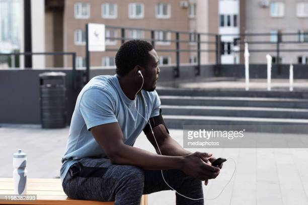 young athletic african american man in sportswear resting on bench in city center and listening to music through earphones after workout - center athlete stock pictures, royalty-free photos & images