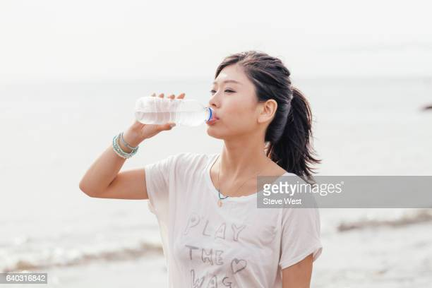 young athletic asian woman drinking water on the beach - thirsty stock pictures, royalty-free photos & images