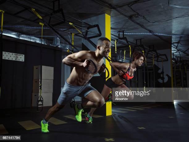 Joven pareja atlética hacer push ups con correas trx