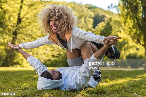 Jeune couple sportif exerçant Acro yoga dans le parc.