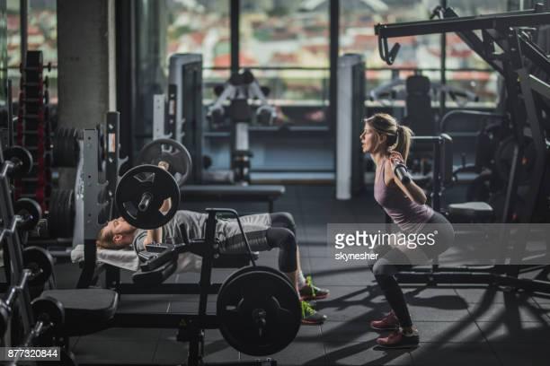 ボディービルのジムでのトレーニングを持っている若い運動のカップル。