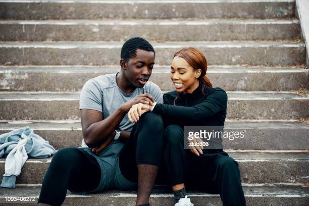 young athletic couple looking at a smart watch before or after running or jogging - smart watch stock pictures, royalty-free photos & images
