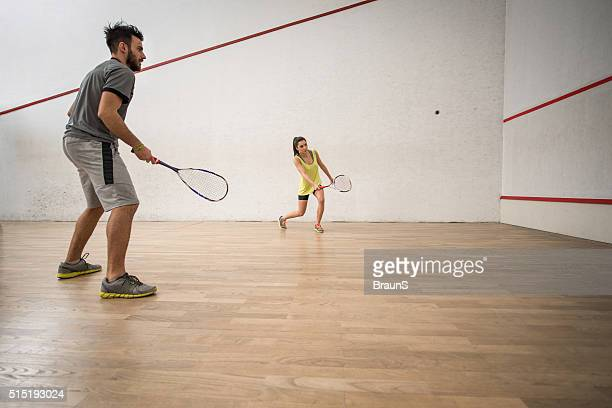 Young athletic couple playing squash on a court.