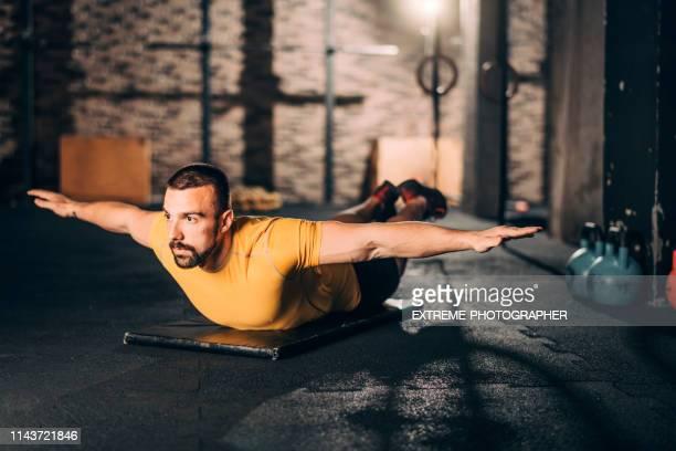joven deportista haciendo una rutina de ejercicios de nadador en su vientre en un gimnasio - acostado boca abajo fotografías e imágenes de stock