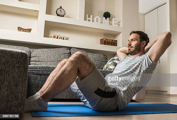 young athletic man doing sit-ups in the living room. - sit ups stock photos and pictures