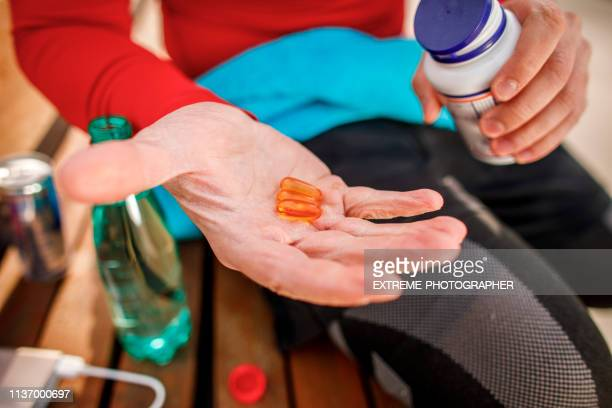 young athletic man holding out a couple of orange colored capsules on the palm of his hand while sitting on a park bench - nutritional supplement stock pictures, royalty-free photos & images