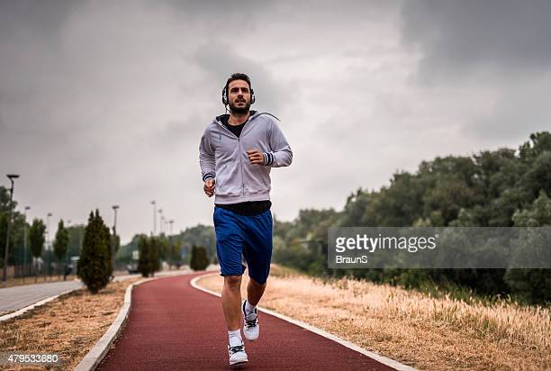 Young athletic man jogging on sports track.