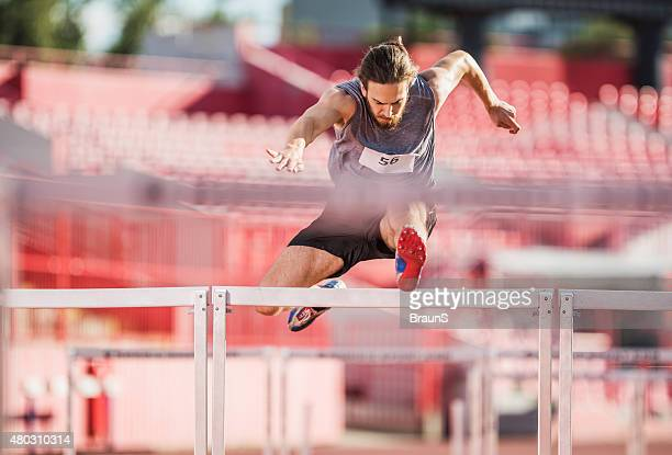young athletic man making an effort while jumping hurdles. - hurdling stock photos and pictures