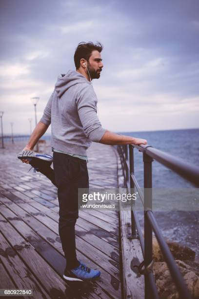 Young athletic man preparing for running next to the sea