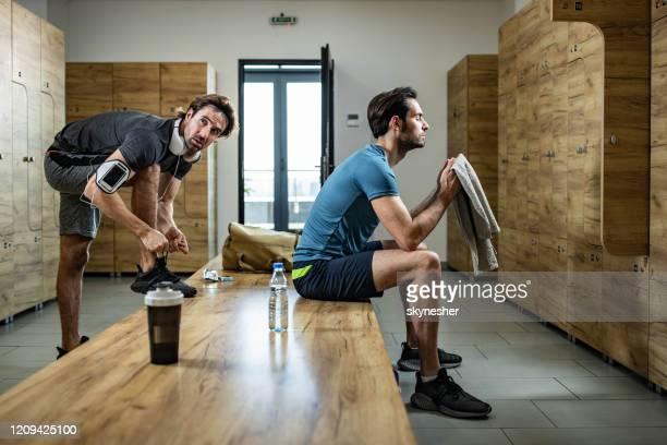 junger athletischer mann, der sich auf das sporttraining in der umkleidekabine des fitnessstudios vorbereitet. - umkleideraum stock-fotos und bilder