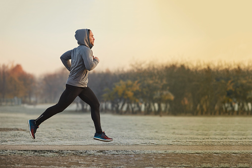 Young athletic man running at park during cold autumn morning 937283086