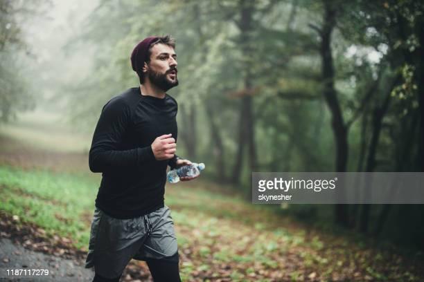 junger athlet, der am herbsttag im park läuft. - joggen stock-fotos und bilder