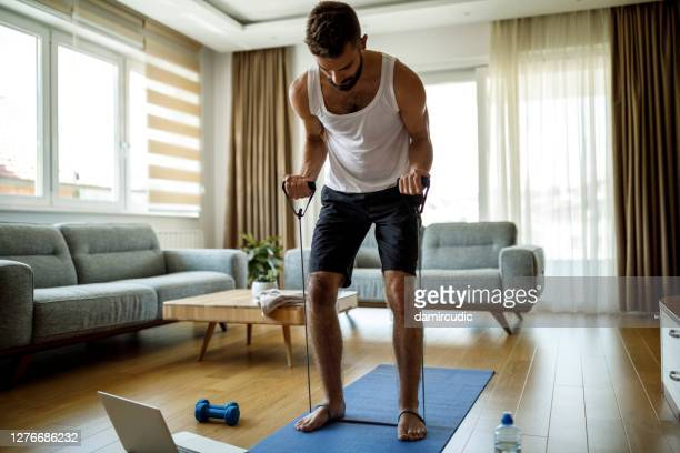 young athletic man training with stretching band at home - strap stock pictures, royalty-free photos & images