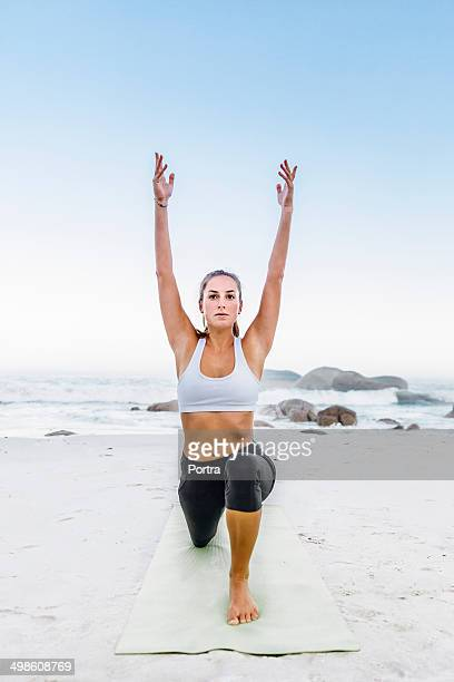 Young athletic woman doing exercise on the beach.