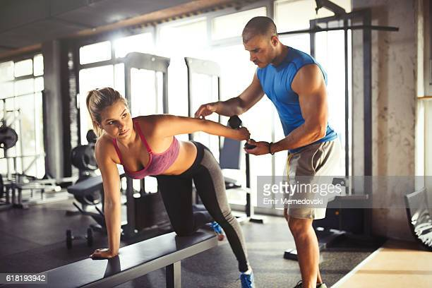 Young athletic woman having weight training with fitness instructor.