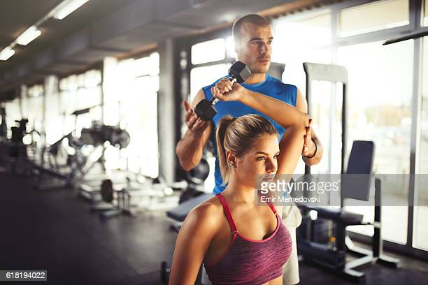 young athletic woman having weight training with fitness instructor. - hand weight stock pictures, royalty-free photos & images