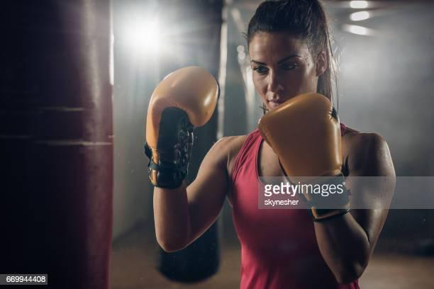 Jeune femme athlétique dans une position de combat sur un entraînement de boxe.