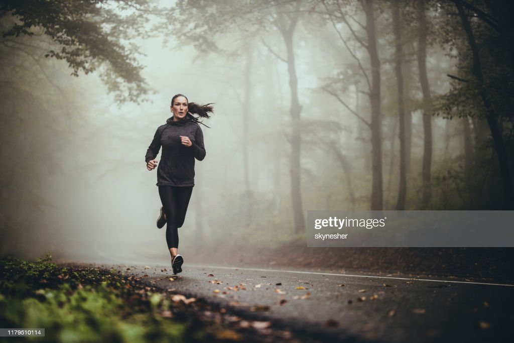 Young athletic woman jogging on the road in foggy forest. : Stock Photo