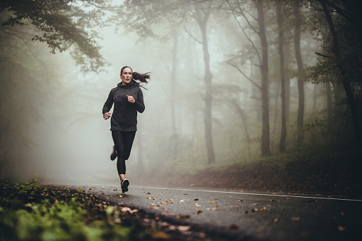 Young athletic woman jogging on the road in foggy forest. 1179510114