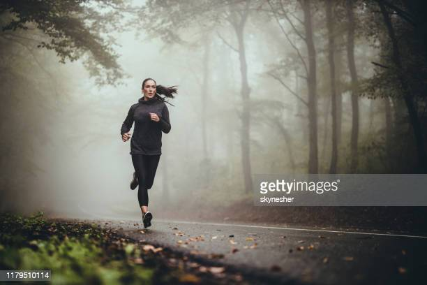 young athletic woman jogging on the road in foggy forest. - termine sportivo foto e immagini stock