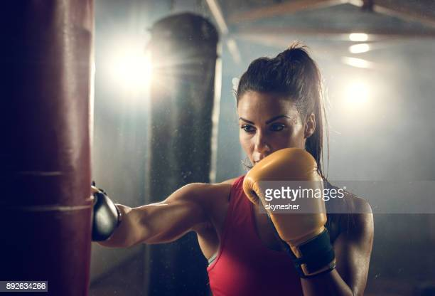Young athletic woman on a boxing training in a health club.
