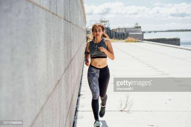 young athletic woman running along a wall - forward athlete stock pictures, royalty-free photos & images